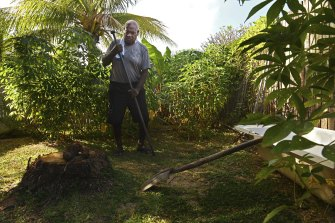Stanley Cook prepares to dig a hole to plant taro in the backyard of his home on the coastline on Thursday Island.