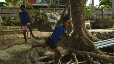 Dereece Cook swings on a rope tied to a tree at his home on the foreshore of Thursday Island watched by his brother Traquiin Cook.