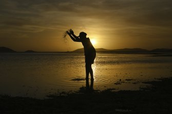 Donniella Warria aged 9 years old plays on the Bach Beach as the sun sets on Thursday Island.