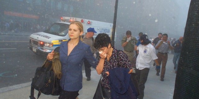 FILE - People flee from downtown Manhattan after planes crashed into the twin towers of the World Trade Center on September 11, 2001 in New York City. Associated Press photographer Richard Drew talks about AP's coverage of 9/11 and the events that followed.