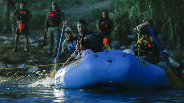 Border Patrol Agents with an inflatable boat help migrants seeking refuge to cross into the U.S., near the banks of the Rio Grande river in Del Rio, Texas