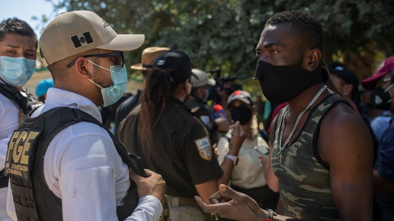 A Haitian migrant pleads with a Mexican police officer blocking access to the Rio Grande river so that immigrants can't use it to cross the U.S.-Mexico border from Ciudad Acuña, Mexico PIC:AP